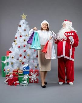 Vue avant du père noël avec jeune femme autour de cadeaux de noël sur fond gris