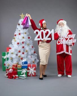 Vue avant du père noël avec jeune femme tenant et joyeux noël sur sol gris noël neige vacances nouvel an présent