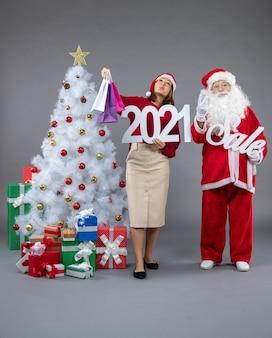 Vue avant du père noël avec jeune femme tenant et vente écritures sur sol gris neige de noël présente vacances nouvel an