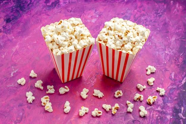 Vue avant du pop-corn frais sur le film de cinéma couleur table rose clair