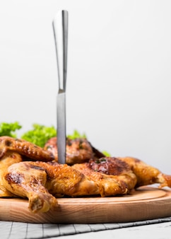 Vue avant du poulet entier cuit sur une planche à découper avec un couteau