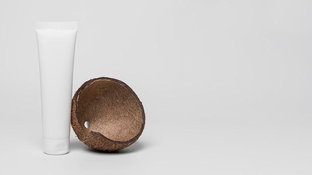 Vue avant du récipient de produit cosmétique vierge avec noix de coco