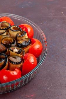 Vue avant du repas de légumes en tranches et tomates roulées aux aubergines sur la surface sombre