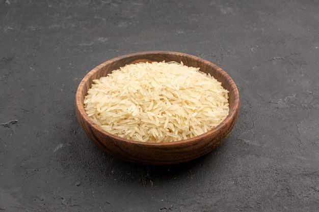 Vue avant du riz cru à l'intérieur de la plaque brune sur l'espace gris