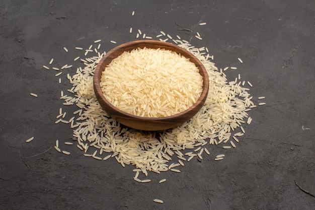 Vue avant du riz cru à l'intérieur de la plaque sur l'espace gris foncé