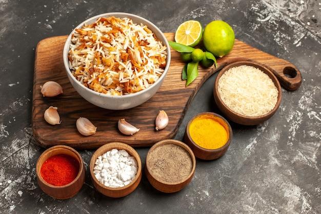 Vue avant du riz cuit avec des assaisonnements sur une surface sombre repas plat sombre east food