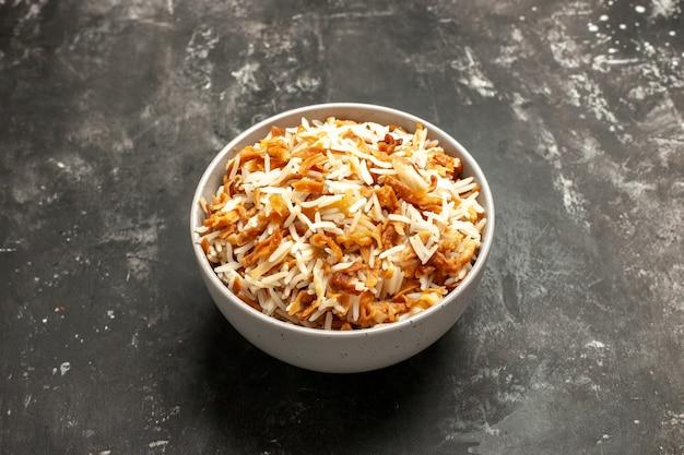 Vue avant du riz cuit à l'intérieur de la plaque sur un plat de surface sombre est repas sombre