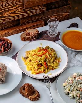 Vue avant du riz cuit avec des légumes frits avec des petits pains à salade et de la soupe sur le sol blanc
