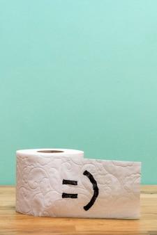 Vue avant du rouleau de papier toilette avec espace copie et visage souriant