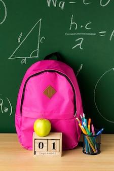 Vue avant du sac à dos de retour à l'école avec pomme et crayons