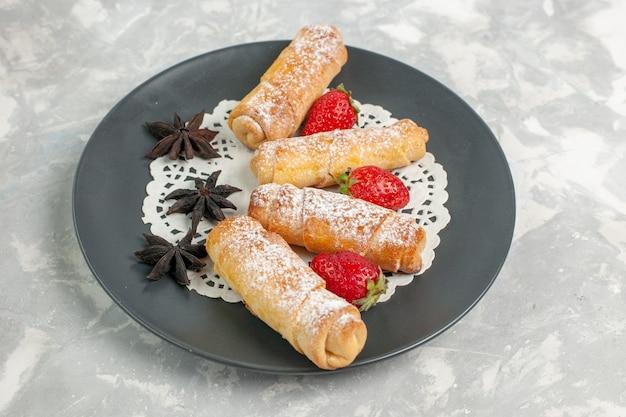 Vue avant du sucre en poudre avec des fraises sur un mur blanc