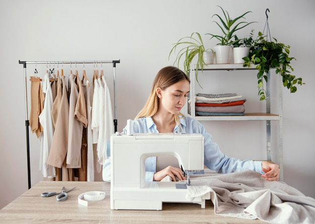 Vue avant du tailleur féminin à l'aide de la machine à coudre dans le studio