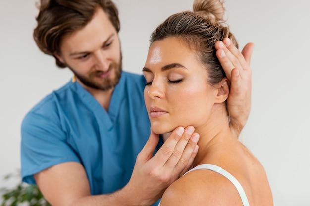 Vue avant du thérapeute ostéopathe masculin contrôle le cou de la patiente