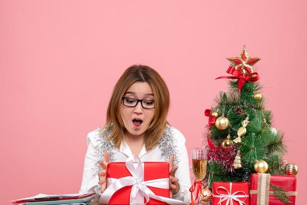 Vue avant du travailleur féminin assis autour de cadeaux de noël et arbre sur rose