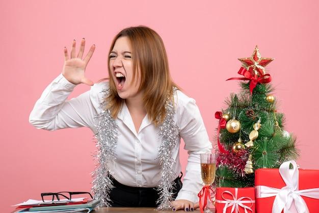 Vue avant du travailleur féminin autour de cadeaux de noël hurlant sur rose