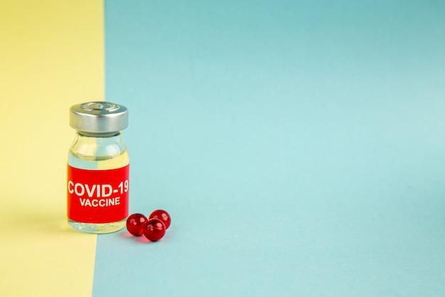 Vue avant du vaccin covid- avec des pilules rouges sur fond jaune-bleu couleur pandémique laboratoire de santé covid- médicament virus hôpital science espace libre