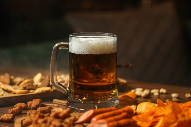 Vue avant du verre de bière avec des collations à la bière croutons chips et saucisses sur la table