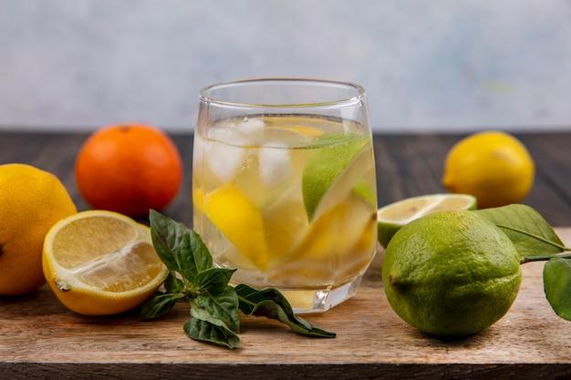 Vue avant du verre d'eau avec des quartiers de citron menthe et de lime sur une planche à découper