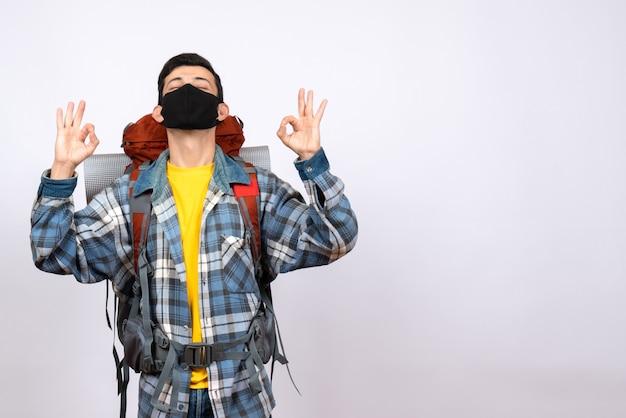 Vue avant du voyageur masculin avec sac à dos et masque faisant signe ok avec les yeux fermés