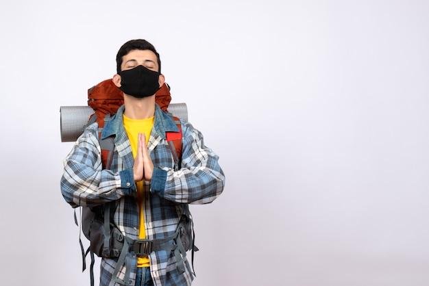 Vue avant du voyageur masculin avec sac à dos et masque joignant les mains
