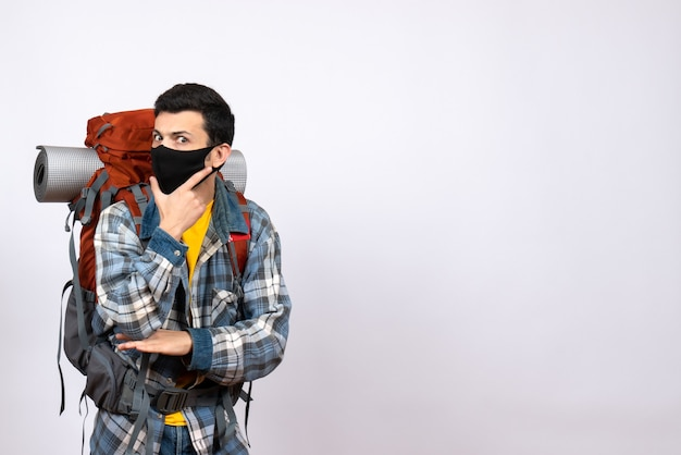 Vue avant du voyageur masculin avec sac à dos et masque mettant la main sur son menton