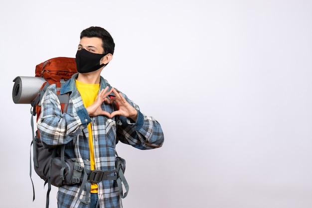 Vue avant du voyageur masculin avec sac à dos et masque noir faisant signe de coeur