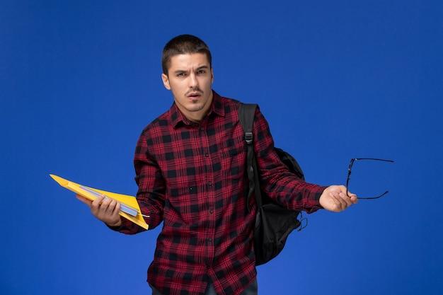 Vue avant de l'étudiant masculin en chemise à carreaux rouge avec sac à dos contenant des fichiers et un cahier sur le mur bleu clair