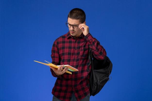 Vue avant de l'étudiant masculin en chemise à carreaux rouge avec sac à dos contenant des fichiers et un cahier sur mur bleu