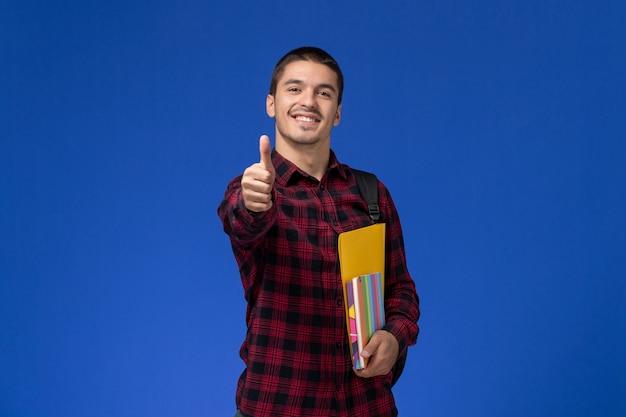 Vue avant de l'étudiant masculin en chemise à carreaux rouge avec sac à dos contenant des fichiers et des cahiers souriant sur mur bleu