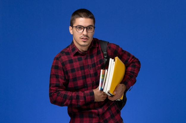 Vue avant de l'étudiant masculin en chemise à carreaux rouge avec sac à dos tenant des cahiers et des fichiers sur un mur bleu clair