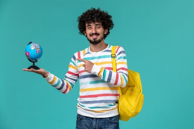 Vue avant de l'étudiant masculin en chemise rayée portant sac à dos jaune tenant petit globe rond sur le mur bleu