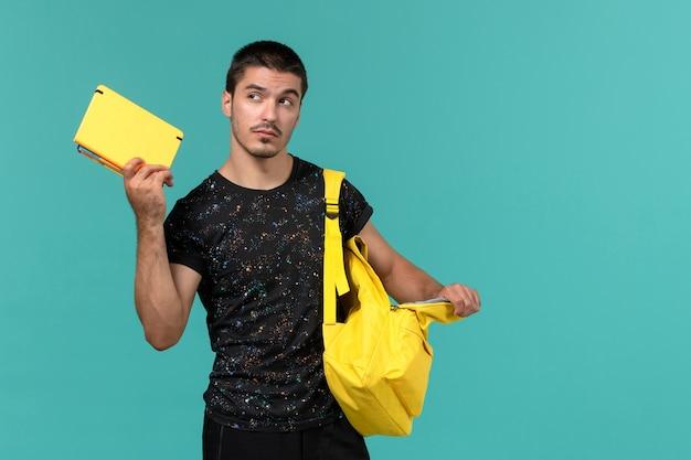 Vue avant de l'étudiant masculin en t-shirt foncé sac à dos jaune tenant un cahier sur un mur bleu clair