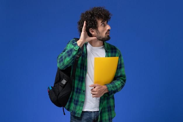 Vue avant de l'étudiant de sexe masculin en chemise à carreaux vert portant un sac à dos noir et tenant des fichiers essayant d'entendre sur le mur bleu