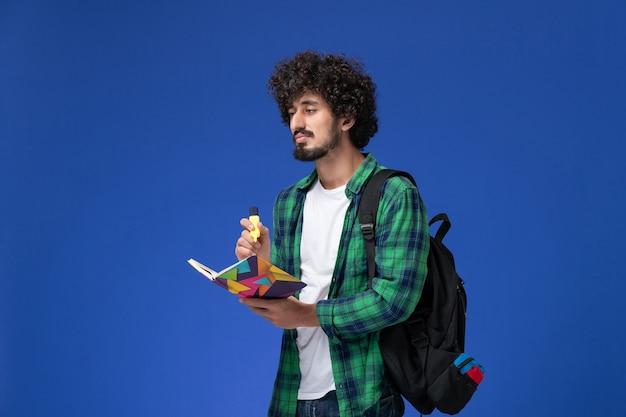 Vue avant de l'étudiant de sexe masculin en chemise à carreaux vert avec sac à dos noir tenant un stylo-feutre et un cahier sur mur bleu