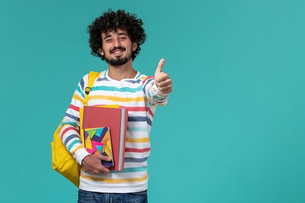 Vue avant de l'étudiant de sexe masculin en chemise rayée de couleur portant un sac à dos jaune tenant des fichiers et des cahiers souriant sur mur bleu