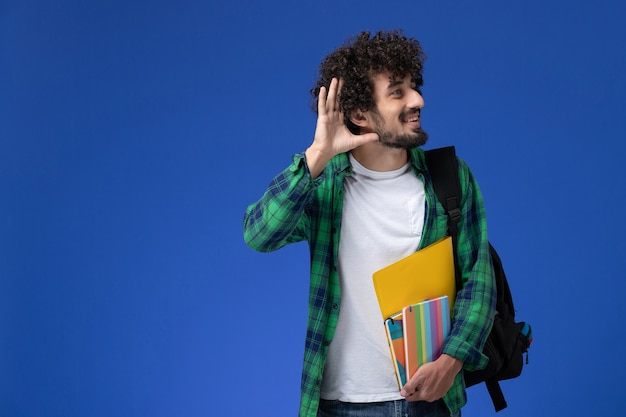 Vue avant de l'étudiant de sexe masculin portant un sac à dos noir tenant des cahiers et des fichiers essayant d'entendre sur le mur bleu