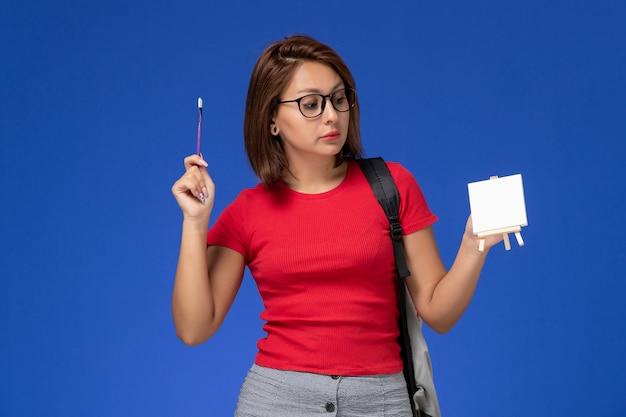 Vue avant de l'étudiante en chemise rouge avec sac à dos peinture petit chevalet sur le mur bleu clair