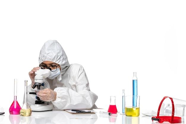 Vue avant femme chimiste en combinaison de protection spéciale contrôle de l'échantillon au microscope sur fond blanc chimie pandémie de virus covid