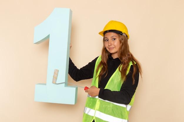 Vue avant femme constructeur en casque jaune peinture numéro un chiffre sur mur blanc