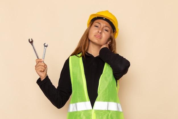 Vue avant femme constructeur en casque jaune tenant des instruments d'argent ayant mal au cou sur bureau léger femme architecte