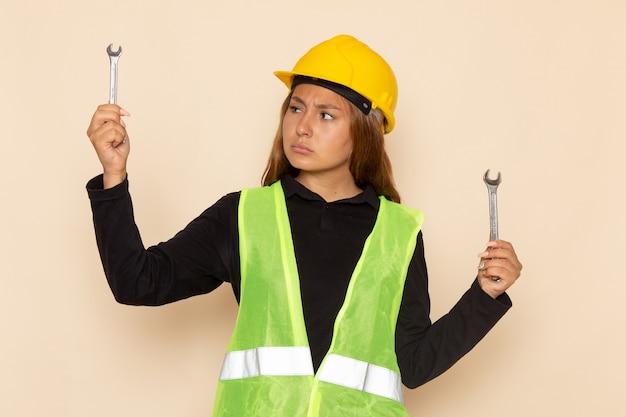 Vue avant femme constructeur en casque jaune tenant des instruments d'argent sur mur blanc femme architecte de construction constructeur