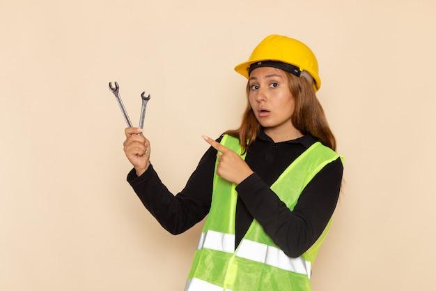Vue avant femme constructeur en casque jaune tenant des instruments d'argent sur le mur de lumière femme architecte