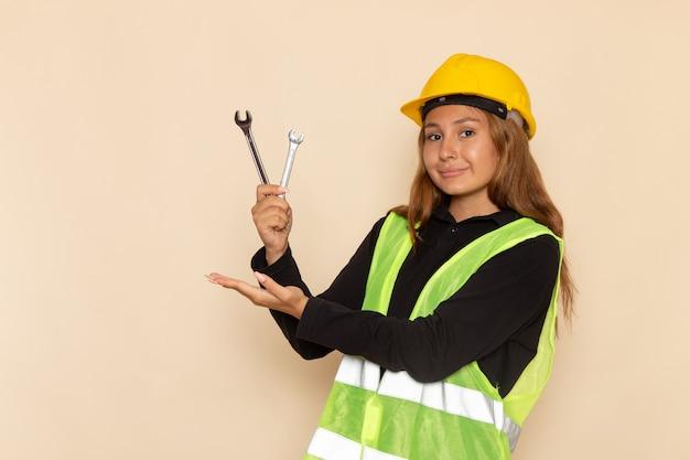 Vue avant femme constructeur en casque jaune tenant des instruments d'argent avec sourire sur mur léger architecte femme