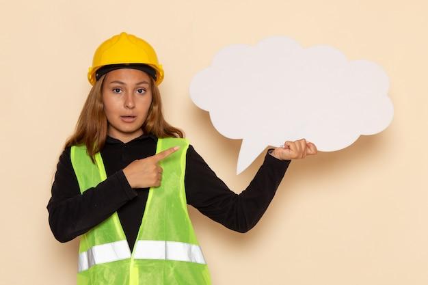 Vue avant femme constructeur en casque jaune tenant une pancarte blanche sur mur blanc femelle