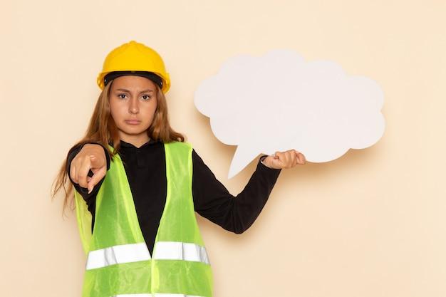 Vue avant femme constructeur en casque jaune tenant une pancarte blanche sur un mur blanc