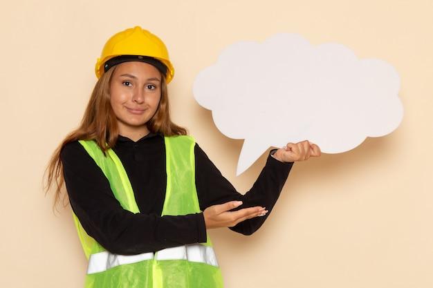 Vue avant femme constructeur en casque jaune tenant une pancarte blanche souriant sur mur blanc femelle