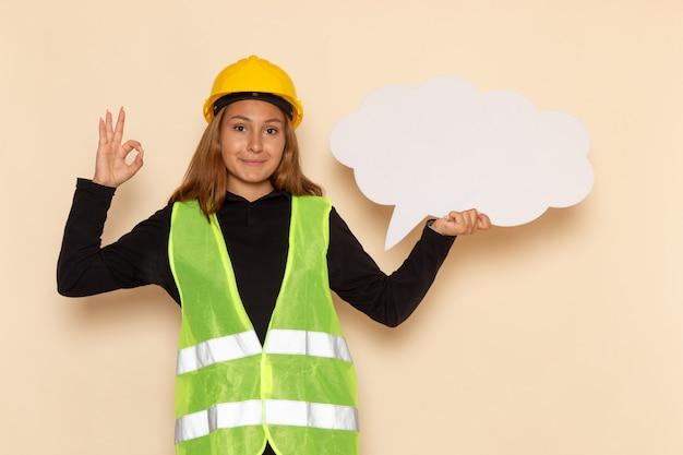 Vue avant femme constructeur en casque jaune tenant une pancarte blanche avec sourire sur mur blanc femelle