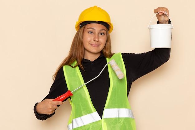 Vue avant femme constructeur en chemise noire casque jaune tenant peinture et pinceau sur mur blanc femme architecte constructeur