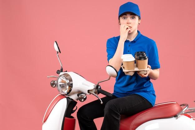 Vue avant femme courrier assis sur le vélo avec des tasses de café sur la couleur rose uniforme de travail de livraison de services alimentaires