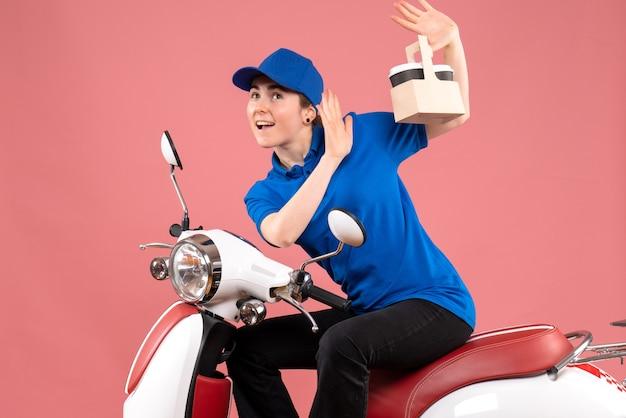 Vue avant femme courrier assis sur le vélo avec des tasses de café sur la livraison de services uniforme de couleur rose nourriture travailleur